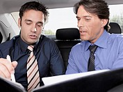 Businessmen working together in back seat of car