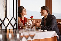 Husband giving wife a rose in elegant restaurant