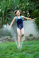 Young girl leaps through yard sprinkler