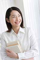 Girl holding textbooks, smiling, front view