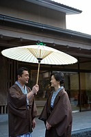 Mature Adult Couple in Yukata Sharing a Paper Umbrella, Side View, Three Quarter Length