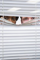 Colleagues looking through blinds