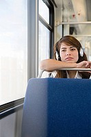 Woman wearing headphones on train