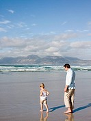 Father and daughter paddling in sea
