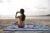 Young woman on beach with camera