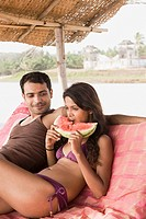 Couple on beach with watermelon