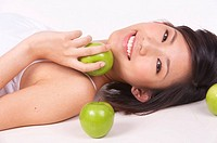 Portrait of Natural Young girl lying on Floor, Holding Apple (thumbnail)