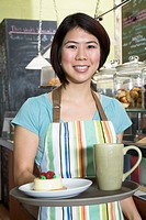 Waitress holding tray in coffee shop