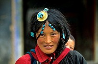 A young woman mother with her son on her shoulders peeping behind her in Gyantze, Tibet, China