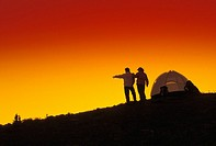 Couple Camping On A Ridge And Watching The Sunset