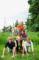 Family forming pyramid in grass