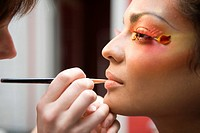 Beautician applying make_up to model, close_up