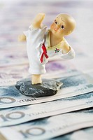 Close_up of a figurine over Chinese currency