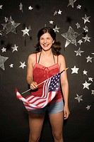 Young woman holding American flag, smiling, portrait