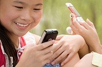 Close_up of a girl using a mobile phone and smiling