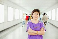 Portrait of a mature woman standing with her arms crossed in a corridor