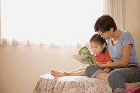 Side profile of a mid adult woman and her daughter reading a book