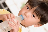Close_up of a boy drinking water from a water bottle