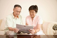 Senior man and a mature woman reading a newspaper