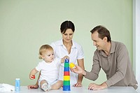 Toddler stacking plastic toys, parents watching (thumbnail)