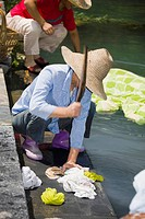 Woman washing clothes at riverside, Xidi, Anhui Province, China