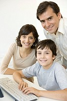 Boy with parents, using keyboard, all smiling at camera