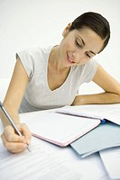 Woman sitting at desk, looking at document and writing in notebook