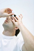 Man applying eye drops, head back