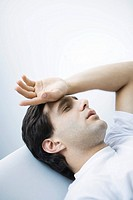 Man reclining with eyes closed, hand on forehead