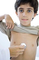 Doctor placing stethoscope on boy's chest, boy smiling at camera, cropped