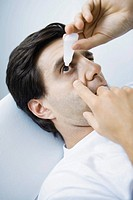 Man reclining, putting eyedrops in one eye (thumbnail)