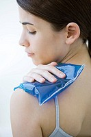 Woman placing cold compress on shoulder, close-up