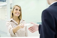 Woman smiling, handing document to businessman