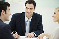 Business associates having discussion, smiling at each other, man taking notes
