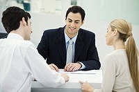 Meeting between professional and clients, together reviewing document