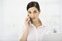 Woman talking on cell phone, looking at camera