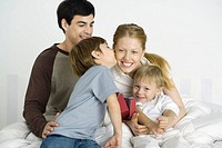 Family sitting together on bed, boy kissing mother's cheek (thumbnail)