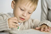 Little boy coloring with crayon, close-up (thumbnail)