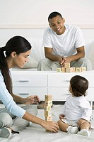 Mother and toddler girl playing with building blocks, daughter looking over shoulder at father in background