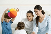 Family gathered around toddler girl, smiling, boy throwing ball in the air