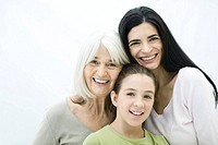 Mother, daughter, and grandmother smiling at camera, portrait