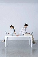 Couple sitting back to back, using laptop computers, holding hands (thumbnail)