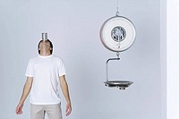 Man standing beside empty scale, balancing can on forehead