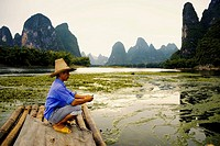 Side profile of a mature man crouching on a bamboo raft with a hill range in the background, Guilin Hills, XingPing, Yangshuo, Guangxi Province, China