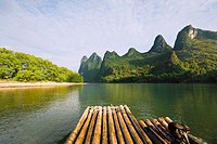 Bamboo raft in a river with a hill range in the background, Guilin Hills, XingPing, Yangshuo, Guangxi Province, China