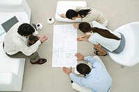 Team of professionals looking at blueprint together, overhead view