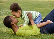 African mother playing with daughter in park