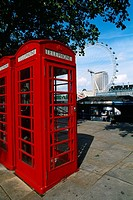 England - London - red telephone booths with ferris wheel in background (thumbnail)