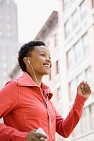 African woman listening to mp3 player while walking outdoors