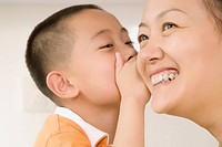 Close_up of a boy whispering to his mother